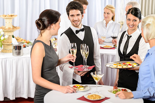 Guest taking champagne from waiter's tray and waitress offering another guest hor d'oeuvres