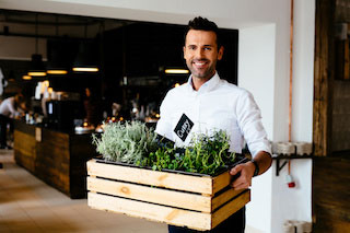 Happy restaurant manager carrying a crate of fresh herbs outside seating area of restaurant