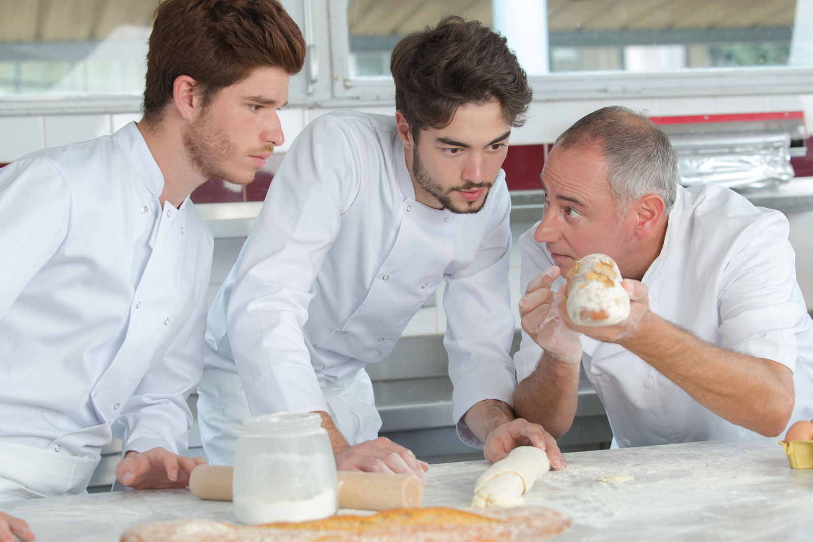 A senior chef holding bread up as two younger chefs examine the composition