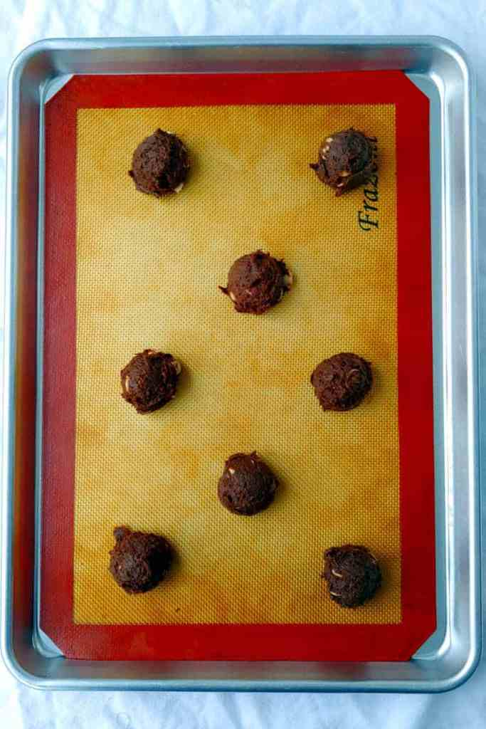 balls of double chocolate caramel chip cookies, unbaked, on a cookie sheet