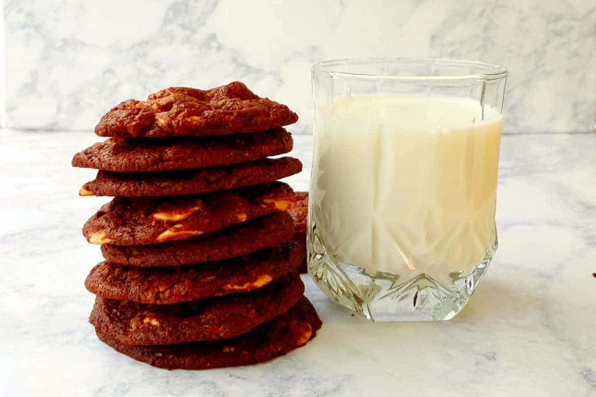 a stack of double chocolate caramel chip cookies next to a glass of milk