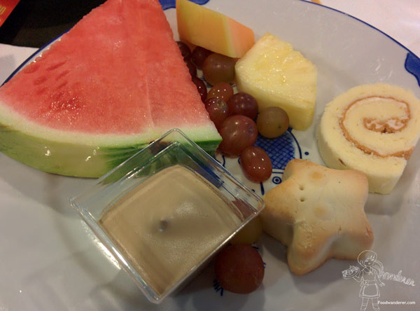 Watermelon slice, grapes, cantaloupe, pineapple, cake roll, star cookie, and coffee pudding