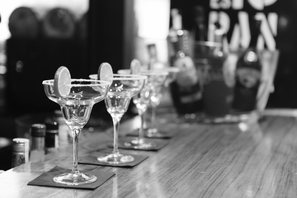 Black and white photo of margarita glasses with limes on a bar | photo by Leeroy via pexels | NJ Restaurants on foodwithaview.com