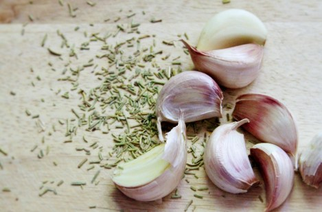 whole purple garlic cloves and dried rosemary on wood cutting board