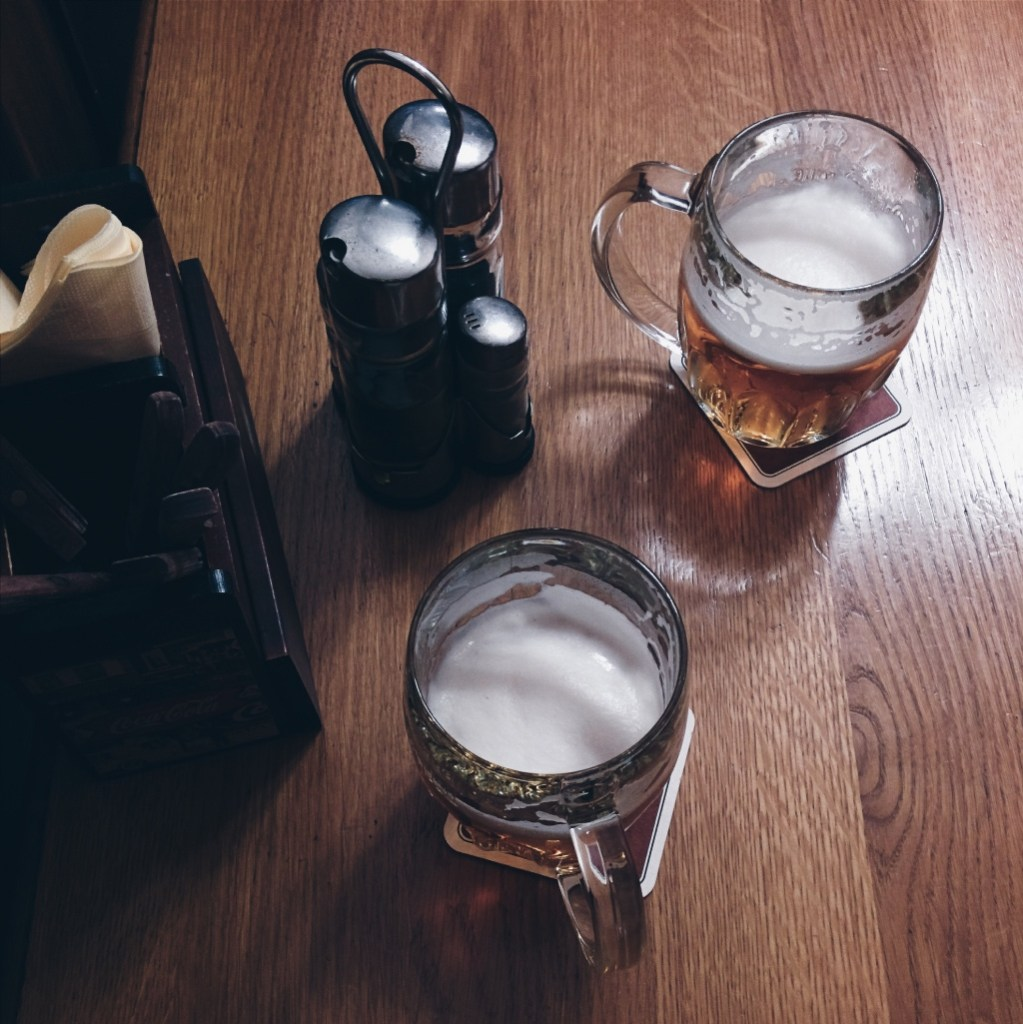 beers in mugs on a wooden table in a bar boxcar