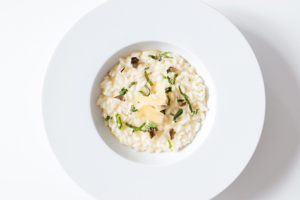 A special date night risotto with fresh parmesan shards in a simple white bowl.