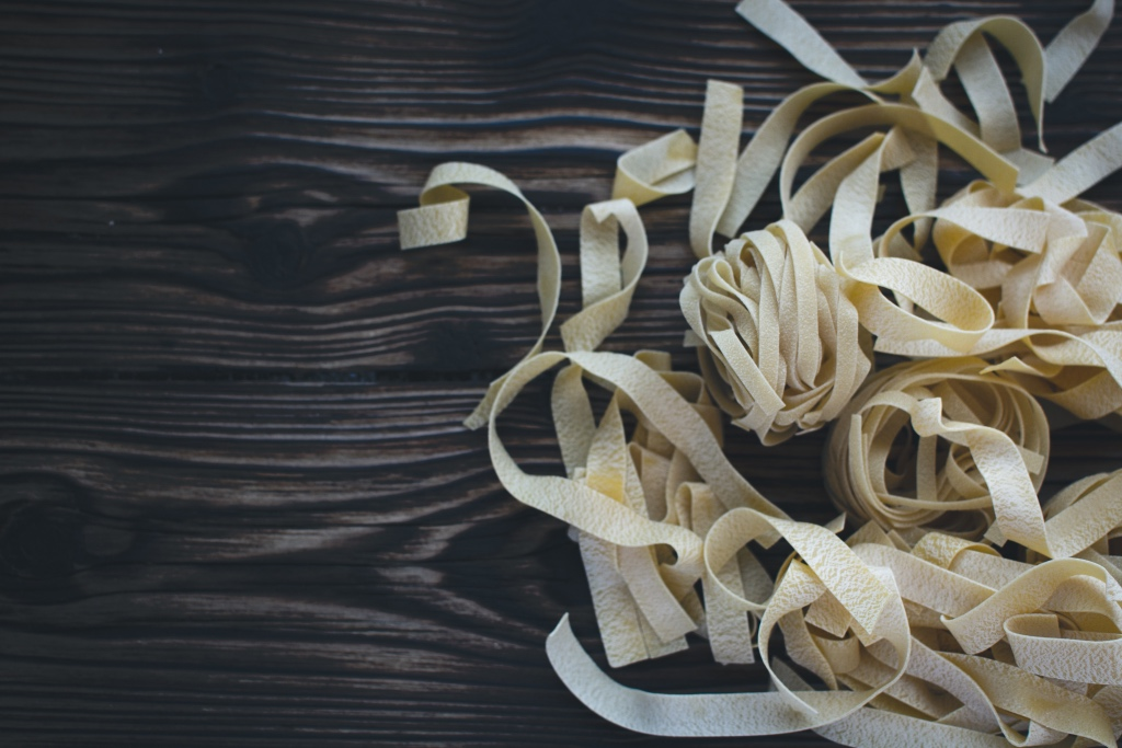 tagliatelle on a dark wooden board by foodiesfeed | valentines day alternatives | foodwithaview.com