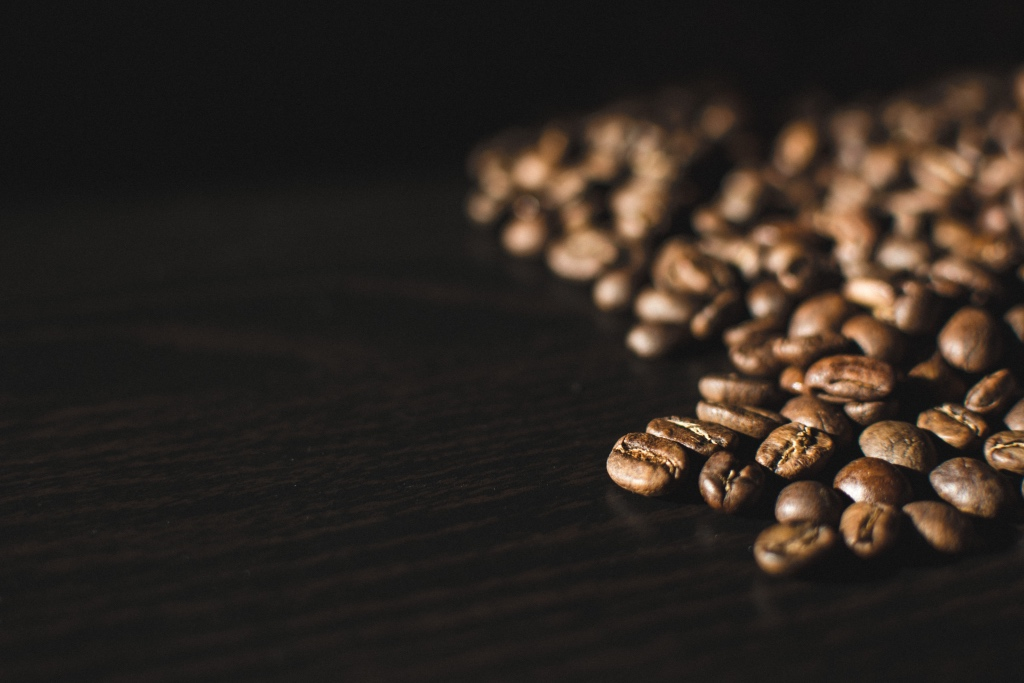 Whole coffee beans on a dark wood table | photo by foodiesfeed | shop local for food and kitchen supplies in northern NJ | foodwithaview.com