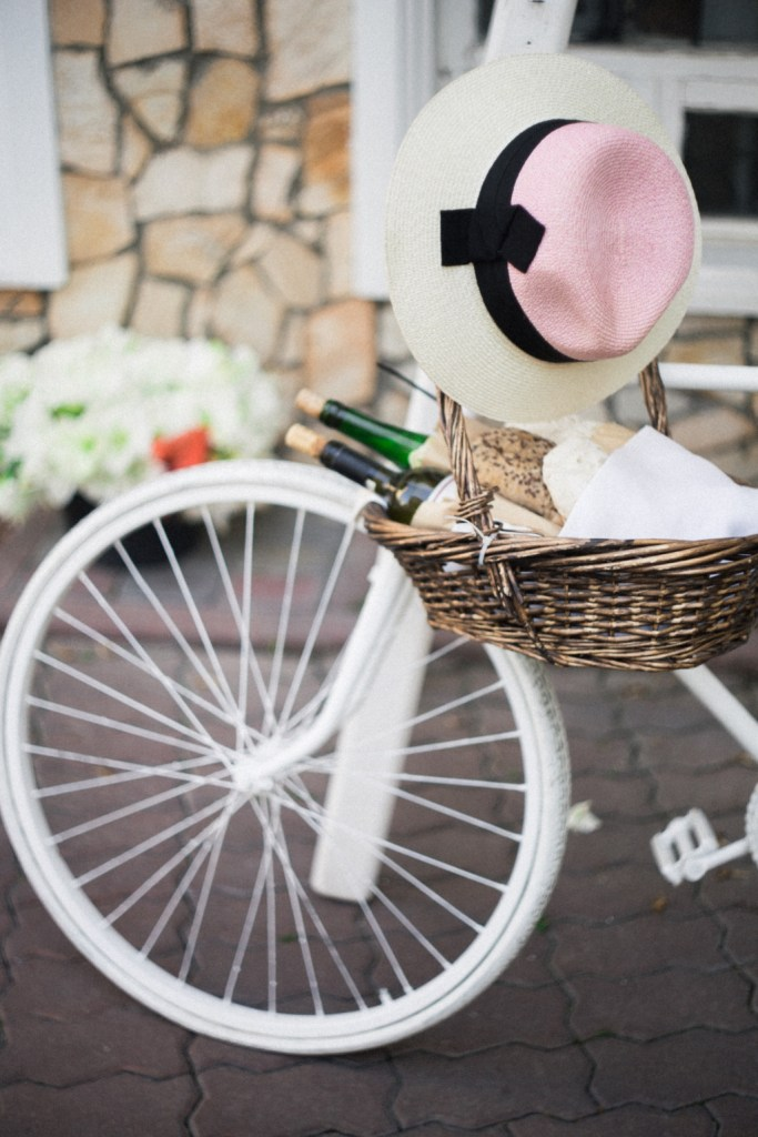 wine bottles in a basket on a white bicycle | photo by angelina litvin via unsplash | adventures in wine country on foodwithaview.com