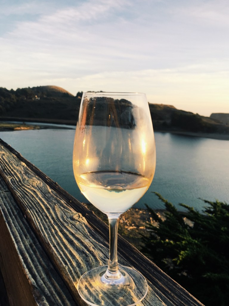 glass of white wine on a ledge overlooking the Russian River in Napa Valley | adventures in wine country on foodwithaview.com