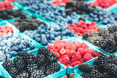 bushels of berries at a farmers market | photo by foodiesfeed | local farm share on foodwithaview.com