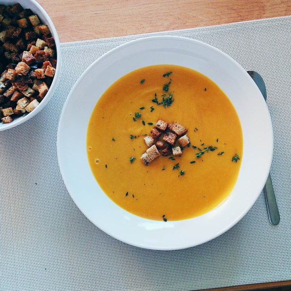 Pumpkin Soup in a white bowl with garnish | Something to warm you up after trick or treating | Halloween party planning on foodwithaview.com