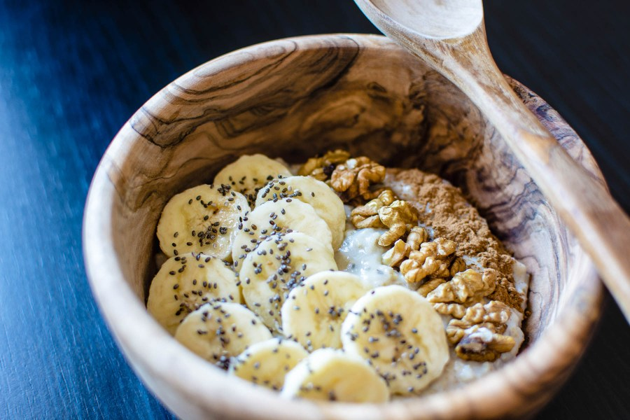 Healthy breakfast of bananas nuts and chia in a wooden bowl | Best NJ Brunch Restaurants on foodwithaview.com | photo by foodiesfeed.com