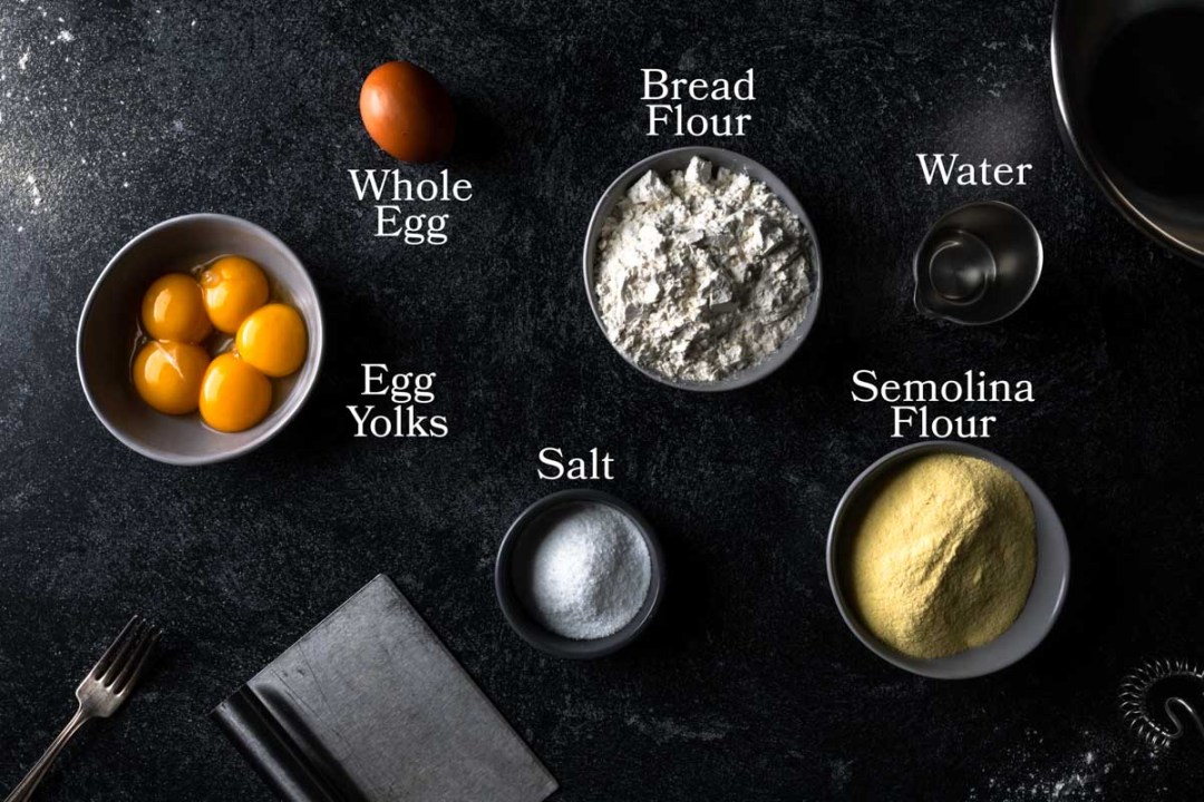 bowls with all the ingredients to make semolina pasta dough: whole egg, egg yolks, bread flour, semolina flour, water and salt for seasoning the cooking water