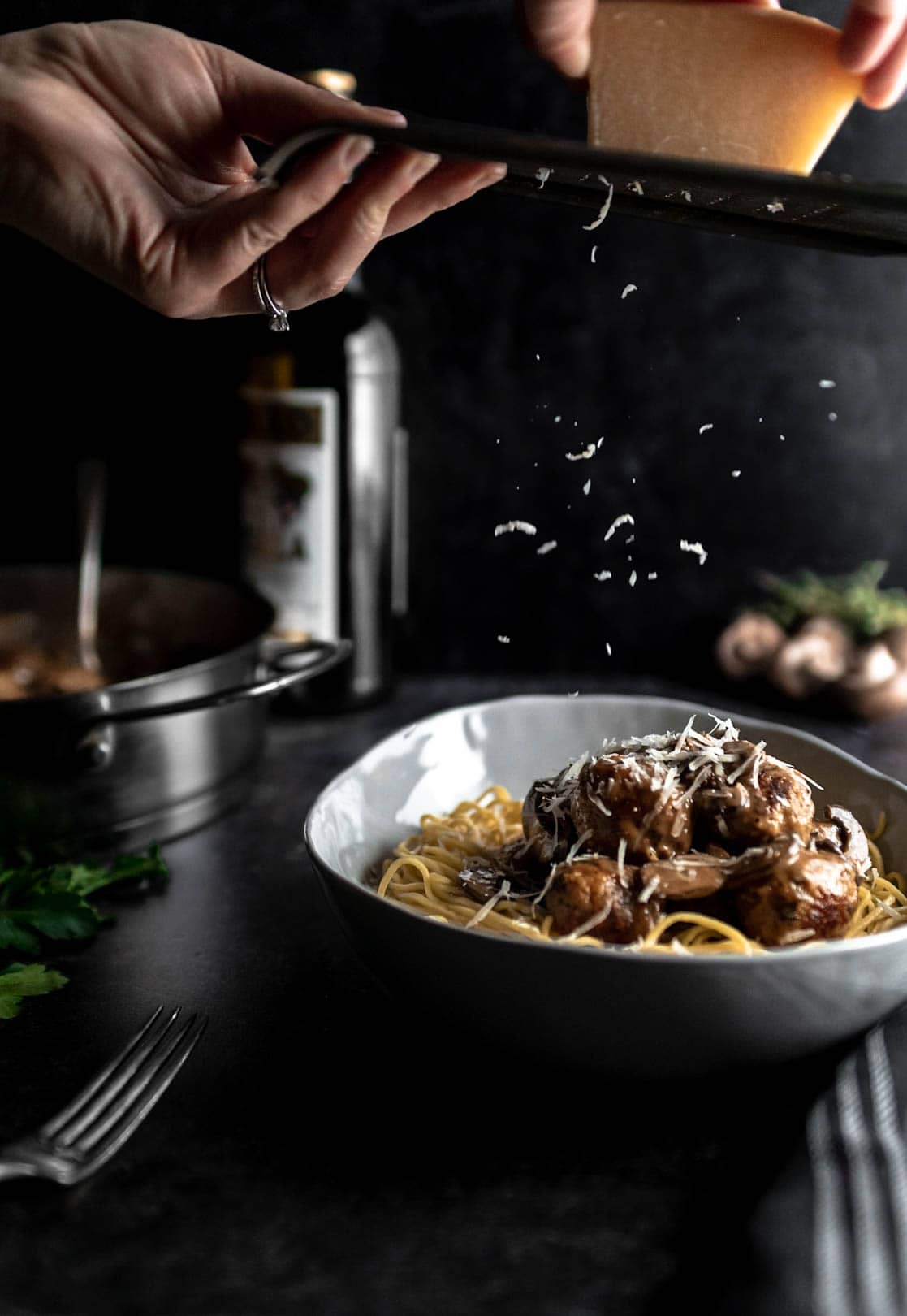 hands shredding parmesan on a cheese grater over a bowl of spaghetti and Chicken Marsala Meatballs