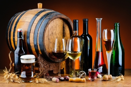 Still life with different alcoholic drinks and wooden barrel.