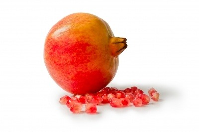 Pomegranate with arils on a white background