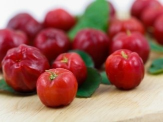 Acerola cherries laid out on a table in both full focus shot with some green leaves.