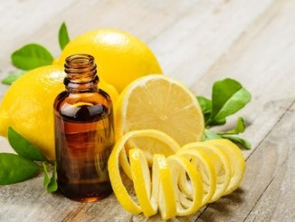 Lemon essential oil and lemon fruit on the wooden board