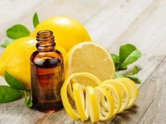 Lemon essential oil and lemon fruit on the wooden board
