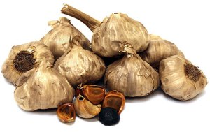 Black garlic cloves and bulbs on a white background.