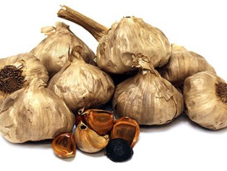 Black garlic bulbs on a white background