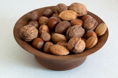 A wooden bowl of nuts. A source of Vitamin E.