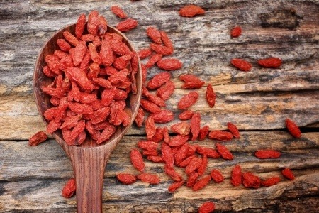 Goji berries on a wooden table and in a spoon.