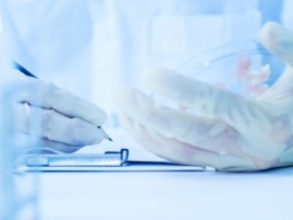 Gloved hands of a microbiologist writing in their note book about the findings of a pour plate.