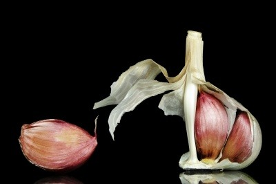 Garlic cloves with one peeled away from the main stem on a black background.