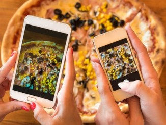 female friends using smartphones to take photos of their pizza