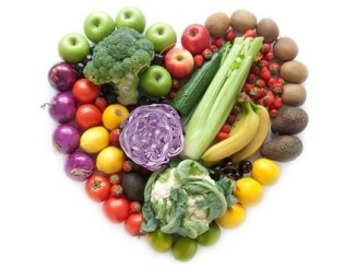 A mix of fruit and vegetables arranged into a heart shape on a white background.