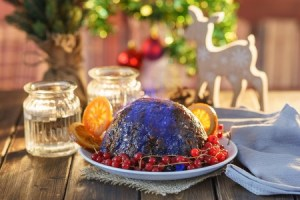Christmas pudding flambe on wooden table in rustic setting.