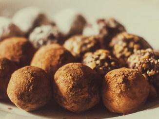 Chocolate truffles arranged on a plate.