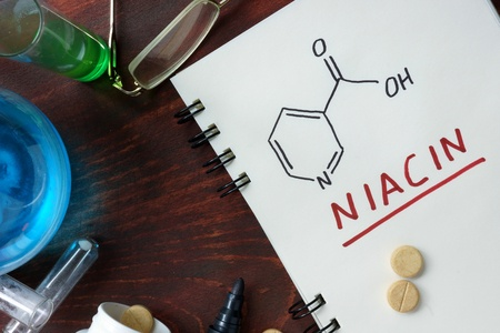 Notepad with chemical formula of niacin (vitamin B3) on the wooden table.