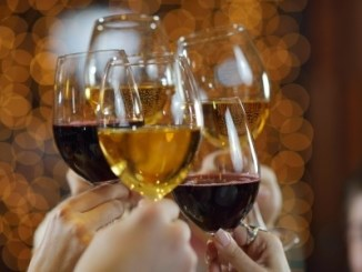 Raise a glass. People lifting their glasses to toast each other or as a greeting.