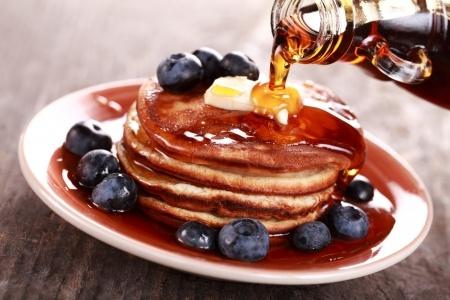 Pouring maple syrup on stack of pancakes.