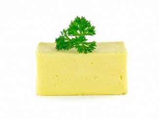 A bar of butter with a parsley leaf on top, on a white background.