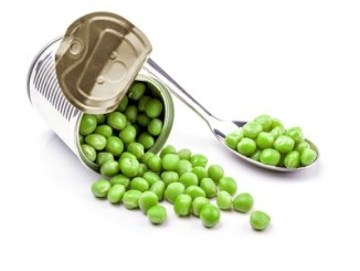 Opened tin with green peas on spoon. Isolated on white background