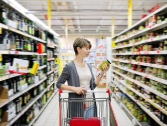 Pretty woman with a cart shopping and choosing goods at the supermarket