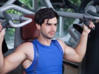 Man in blue vest doing shoulder press.
