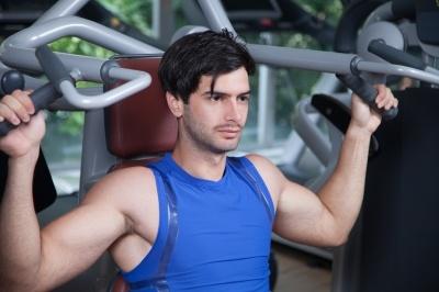 Man in blue vest doing shoulder press.