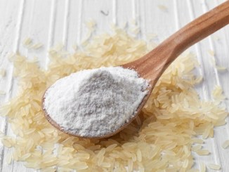 Spoon of rice flour on white wooden background