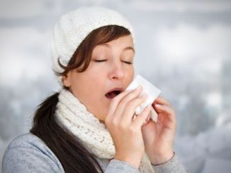 Woman with a cold holding a tissue (without snow in background).