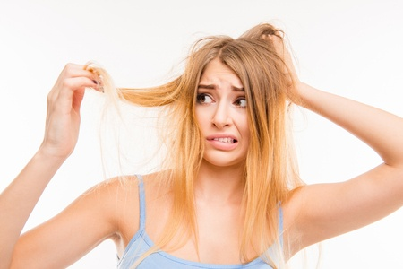 Sad girl looking at her damaged hair. Copyright: deagreez / 123RF Stock Photo