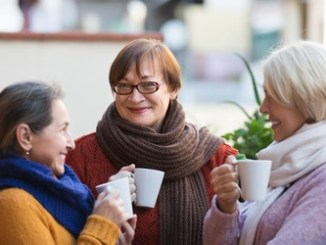 Portrait of smiling senior female friends drinking coffee at patio