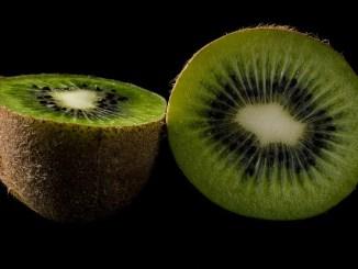 Kiwi fruit halves on a black background.
