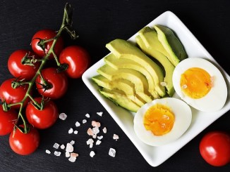 Tomatoes, avocado, egg on a white dish with black background. Foods for a keto diet.