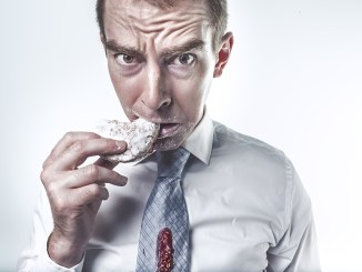 man eating a sweet snack in a shirt and tie. sugar tax.