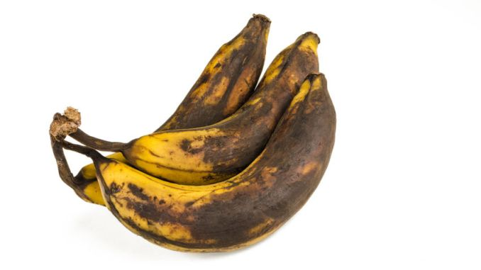 Bunch of over ripe bananas on white background